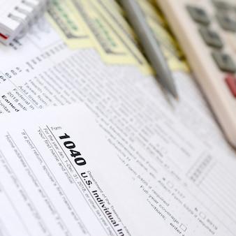 La penna, taccuino, calcolatrice e banconote da un dollaro