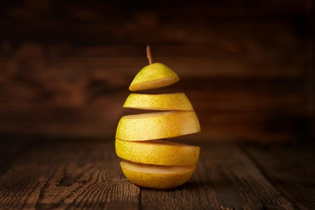La pera vola su fondo di legno, tagliere, frutta, levitazione, volo.