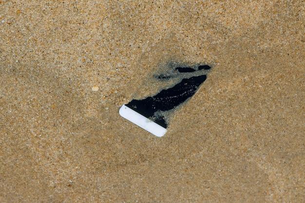 La perdita del telefono cellulare cade nell'acqua del mare vicino alla spiaggia.