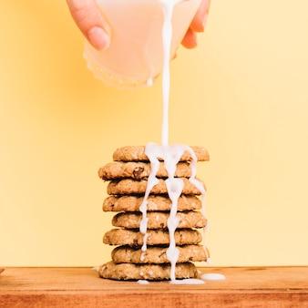 La persona che versa il latte dal vetro sulla pila di biscotti