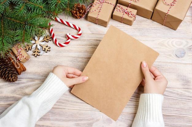 La persona detiene la carta e la busta di buon natale