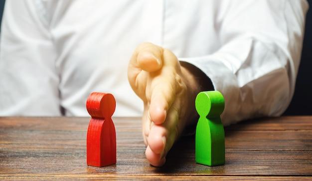 La persona divide con il palmo le figure rosse e verdi delle persone.