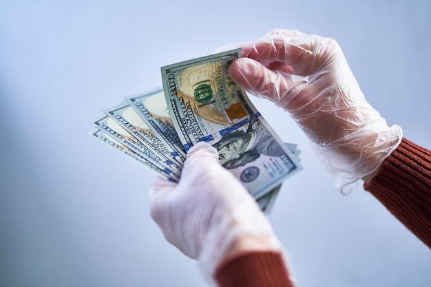 La persona in guanti protettivi trasparenti conta banconote da un dollaro. salute e protezione delle mani dai virus