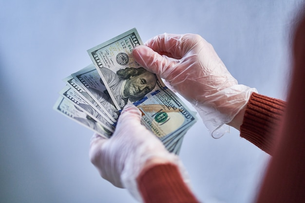 La persona in guanti trasparenti detiene banconote da un dollaro durante l'epidemia di virus dell'influenza e l'epidemia di coronavirus.
