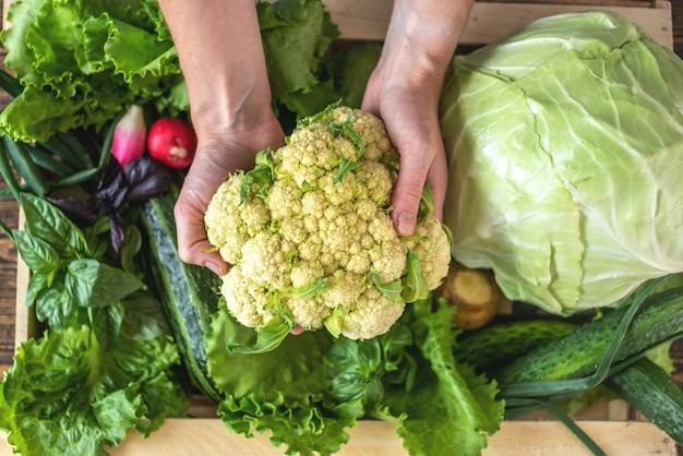 La persona sta estraendo le verdure fresche da una scatola di legno