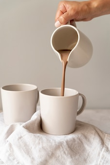 La persona versa il caffè in tazza bianca