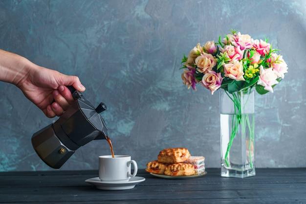 La persona versa il caffè moka caldo dell'aroma in una piccola tazza bianca durante il tempo del caffè