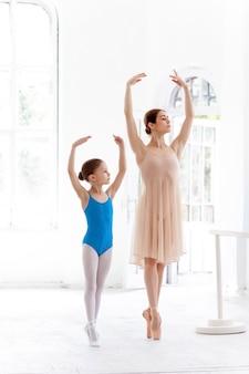 La piccola ballerina in posa alla sbarra di balletto con insegnante personale in studio di danza