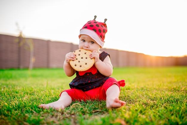 La piccola bambina con un grande biscotto al cioccolato si siede sul cortile