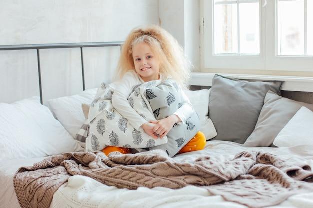 La piccola bella ragazza bionda riccia ha svegliato e che sorride, mor accogliente