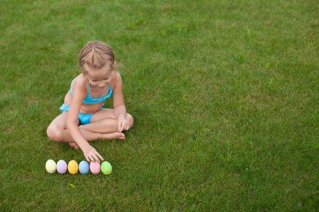 La piccola bella ragazza considera le uova di pasqua su erba verde