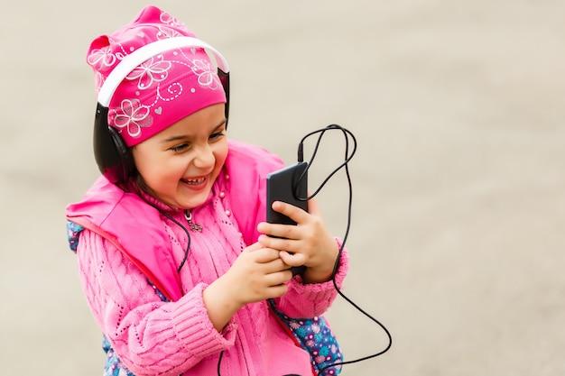 La piccola bella ragazza gode del telefono. lei cuffie. bambini e tecnologia