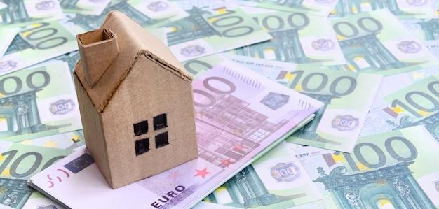 La piccola casa del giocattolo è situata su un insieme di denominazioni monetarie verdi di 100 euro