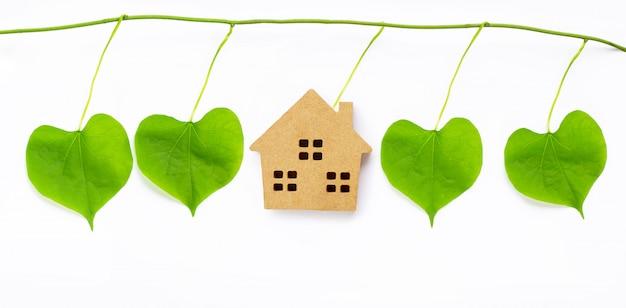 La piccola casa di legno con il cuore delle foglie verdi ha modellato su bianco