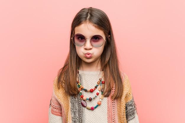 La piccola donna del hippie soffia le guance, ha espressione stanca. concetto di espressione facciale.
