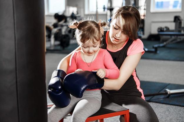 La piccola donna sta praticando la boxe, la donna insegna alla mamma a box, madre e figlia divertenti in palestra, madre e figlia felici in palestra ruolo emotivo di genere maschile