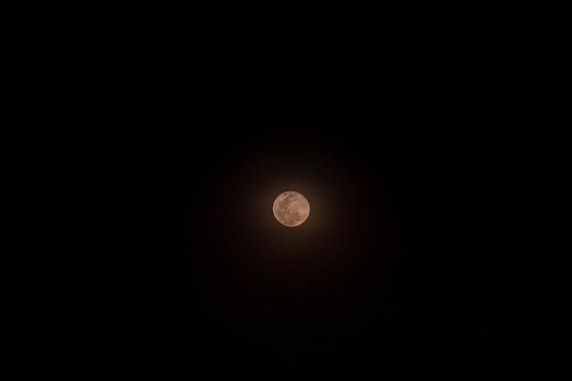 La piccola luna piena isolata sopra il nero