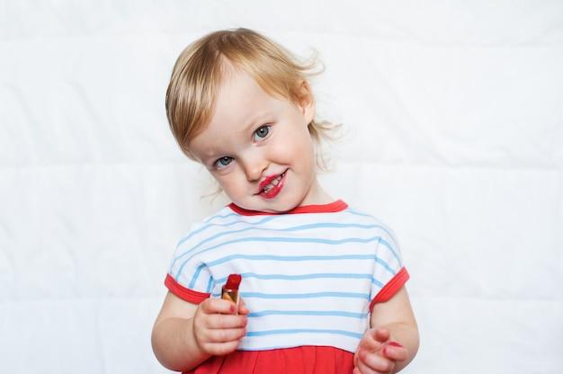 La piccola neonata bionda divertente compone le labbra con il rossetto rosso della mamma. imparare ad essere donna.