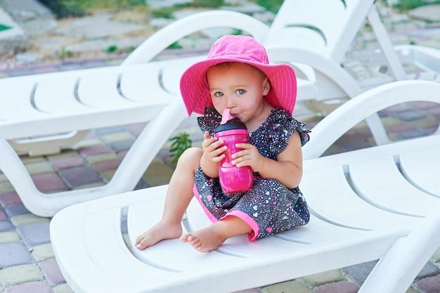 La piccola neonata nel parco di autunno beve dalla bottiglia di plastica rosa