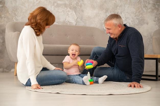 La piccola neonata raccoglie una piramide con i nonni al salone. la famiglia trascorre del tempo insieme indoor, livestile