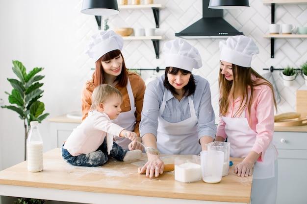 La piccola neonata sta sedendosi sul tavolo di legno alla cucina mentre sua madre, la zia e la nonna stanno producendo l'impasto per i biscotti. donne felici in grembiuli bianchi che cuociono insieme