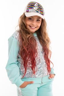 La piccola ragazza abbastanza caucasica in una tuta sportiva sorride, maschera isolata su bianco