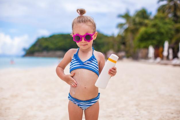 La piccola ragazza adorabile in costume da bagno si strofina la protezione solare