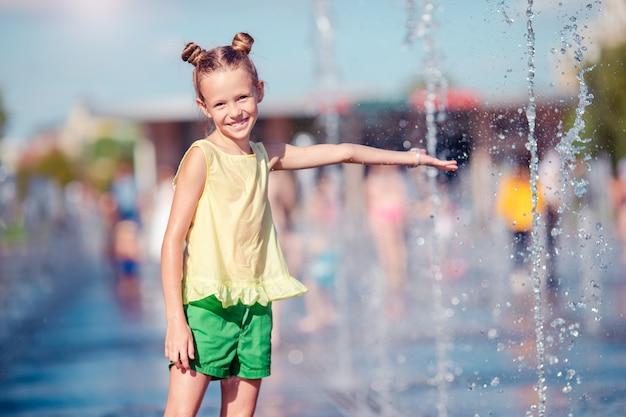 La piccola ragazza adorabile si diverte in fontana della via al giorno soleggiato caldo