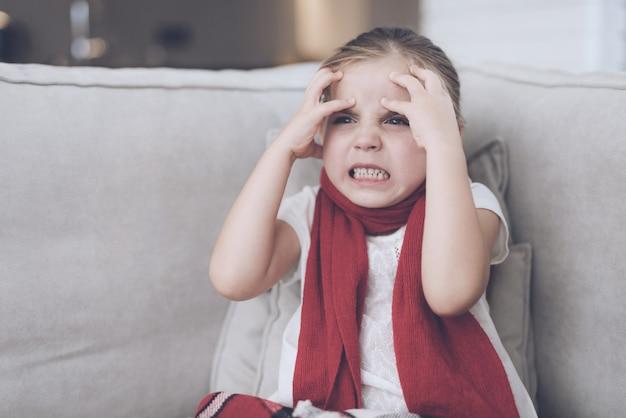 La piccola ragazza ammalata tiene le sue mani vicino alla sua testa.