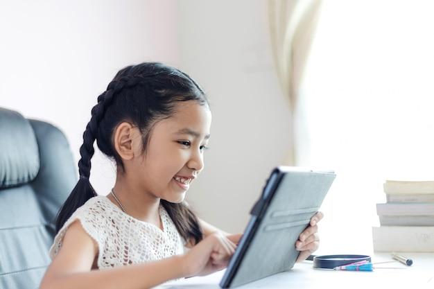 La piccola ragazza asiatica che per mezzo della compressa e sorride con felicità per concetto selezionato di istruzione mette a fuoco la profondità di campo bassa