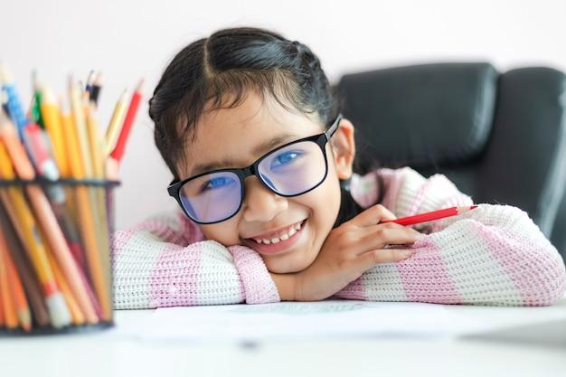 La piccola ragazza asiatica che tiene la matita a fare i compiti e sorride con felicità per la profondità di campo selezionata del fuoco di concetto di istruzione bassa