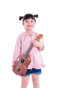 La piccola ragazza asiatica che tiene le ukulele e sorride sopra fondo bianco
