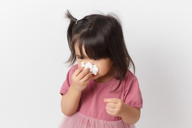 La piccola ragazza asiatica che tiene un tessuto e soffia il suo naso. capretto con rinite fredda.