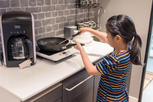 La piccola ragazza asiatica chld prova a cucinare indipendentemente, cucinando il concetto