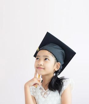 La piccola ragazza asiatica del ritratto sta indossando il cappello laureato e sorride con felicità