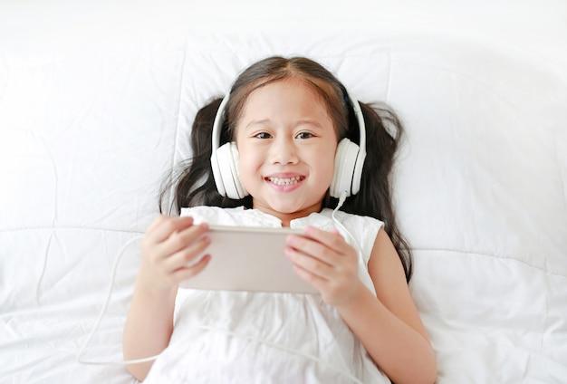 La piccola ragazza asiatica felice che usando le cuffie ascolta musica dallo smartphone che sorride e che guarda la macchina fotografica.