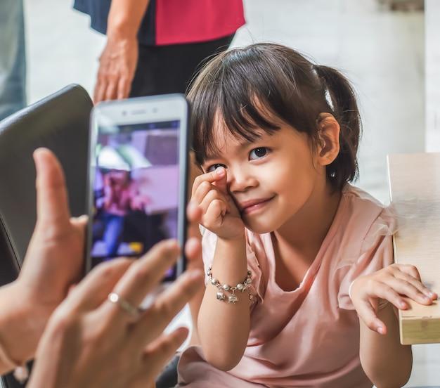 La piccola ragazza asiatica prende una foto con uno smartphone.