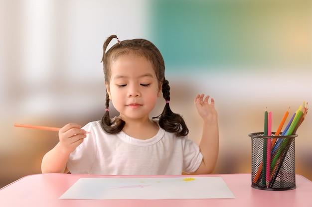 La piccola ragazza asiatica riccia gode di di disegnare a casa. concetto di educazione.