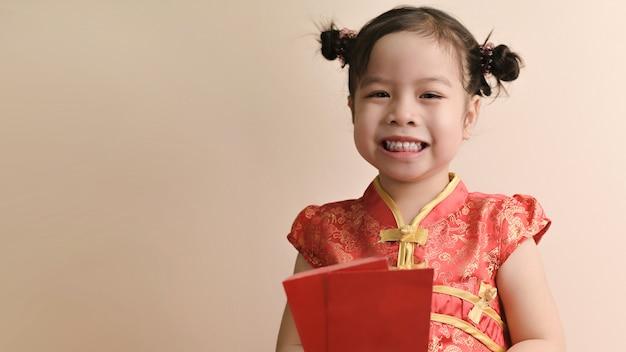 La piccola ragazza asiatica riccia sorridente tiene le buste e il sorriso rossi