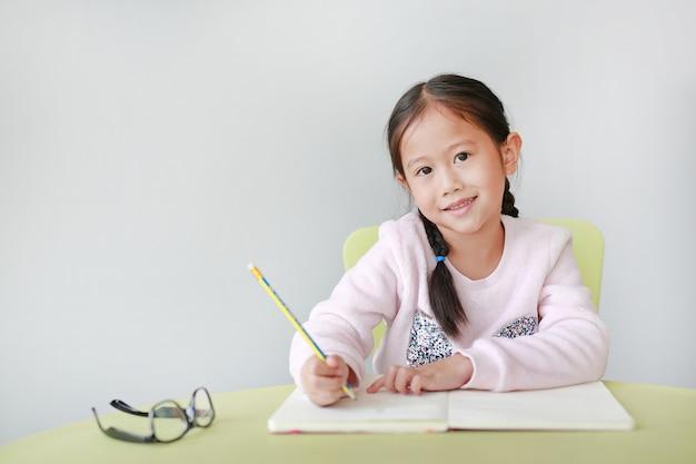 La piccola ragazza asiatica sorridente del bambino scrive in un libro o in un taccuino con la matita sulla tavola in aula.