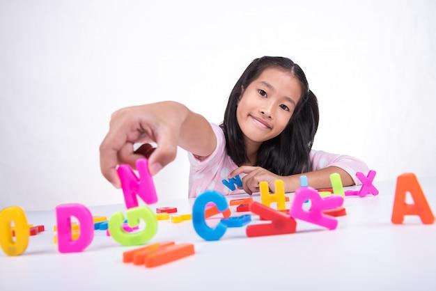 La piccola ragazza asiatica sta imparando con il modello del giocattolo di abc