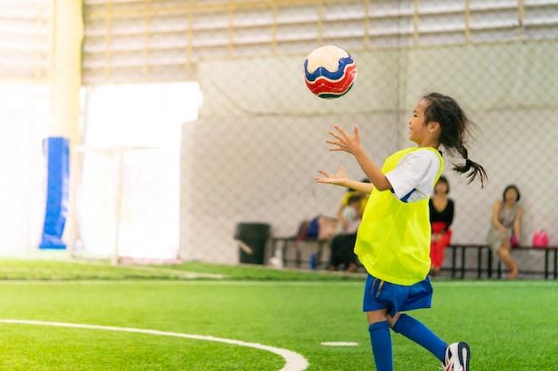 La piccola ragazza asiatica sta preparandosi nel campo di calcio dell'interno