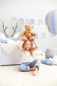La piccola ragazza bionda che tiene un orsacchiotto riguarda la parete di un pallone decorativo. il bambino gioca nella stanza dei bambini con i giocattoli. il concetto di infanzia, viaggi. bambino all'asilo. interno