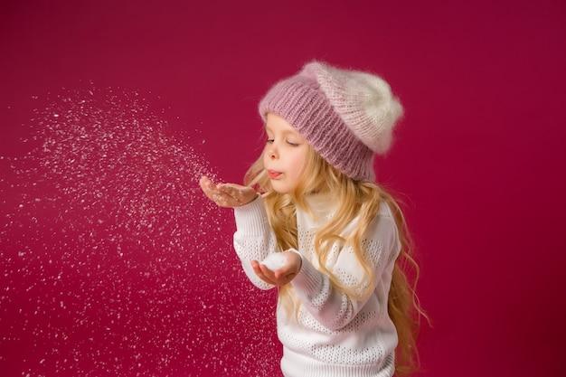 La piccola ragazza bionda con il cappello e il maglione tricottati gioca con la neve