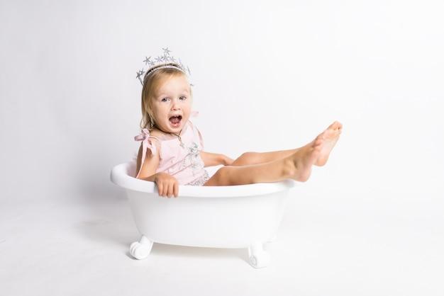 La piccola ragazza bionda divertente si siede in un bagno nello studio