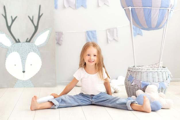 La piccola ragazza bionda in maglietta e jeans si siede vicino ad un pallone decorativo. il bambino divertente gioca vicino al pallone nella stanza dei bambini. il concetto di infanzia, creatività. compleanno, decorazioni natalizie