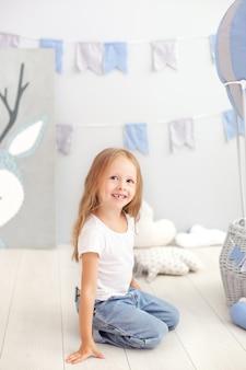 La piccola ragazza bionda in maglietta e jeans si siede vicino ad un pallone decorativo. il bambino divertente gioca vicino al pallone nella stanza dei bambini.