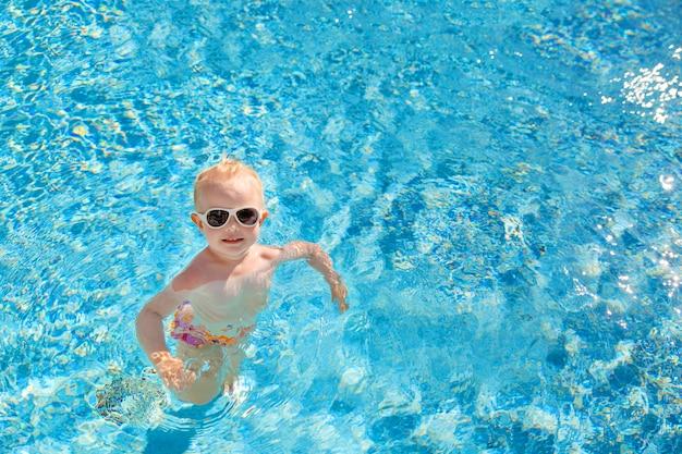 La piccola ragazza bionda nuota nello stagno con acqua blu