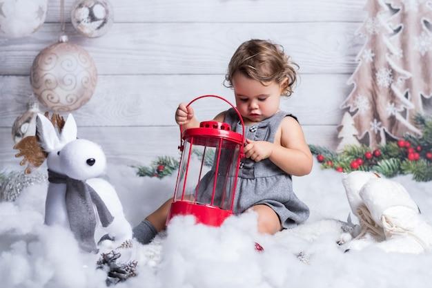 La piccola ragazza bionda sta giocando nella decorazione dell'inverno di natale.