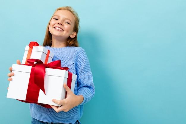 La piccola ragazza caucasica tiene le scatole bianche con i regali e si rallegra isolato sul blu